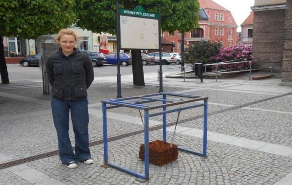 kobieta stoi przy metalowym pomniku