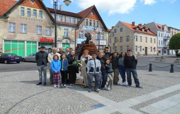 ludzie stoją przy metalowej rzeźbie
