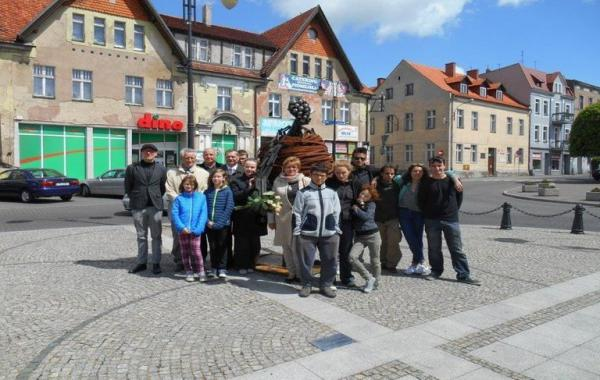 ludzie stoją na pacu przy rzeźbie