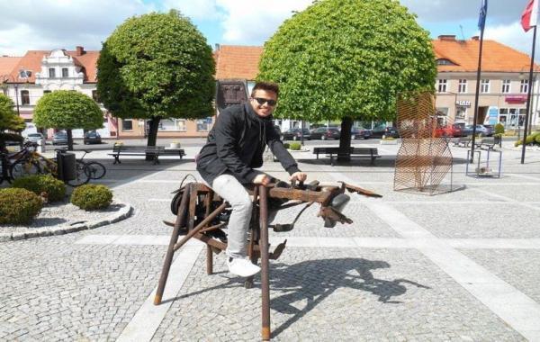 mężczyzna siedzi na metalowej rzeźbie