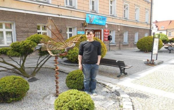 mężczyzna stoi przy rzeźbie
